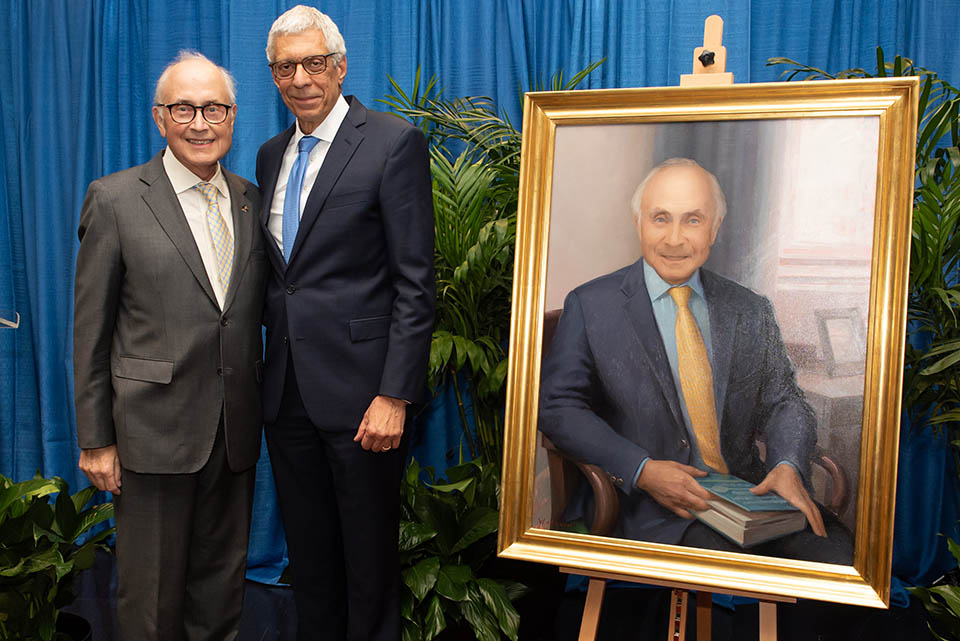 Robert Wilmott, M.D., left, and University President Fred P. Pestello, Ph.D., pose next to Wilmott's new portrait. The portrait was unveiled Friday, Oct. 22, during a ceremony. Photo by Luke Yamnitz.