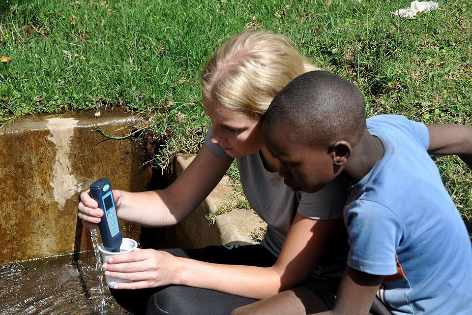 SLU student Lauren Beduhn (left) demonstrates water testing to a resident of Esther House.