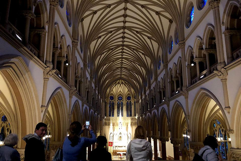 Pilgrims take in a view of the nave of St. Francis Xavier College Church from the choir loft.