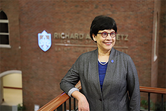 Dr. Barnali Gupta stands inside the Chaifetz School of Business. The school's logo is visible in the background. Dr. Gupta is smiling and wears a gray blazer with a blue Chaifetz School pin.