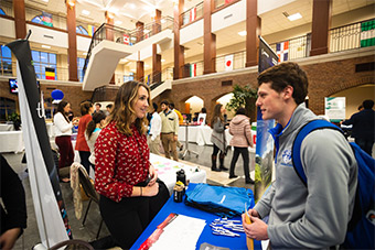 A male SLU student speaks to a female career recruiter at a 2018 networking event. The event took place in the main atrium of the Chaifetz School of Business.