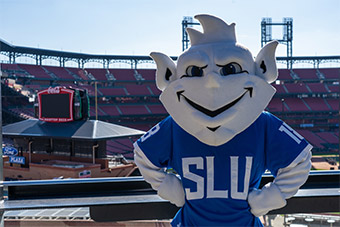 The SLU Billiken mascot poses for a picture at Busch Stadium on a sunny day.