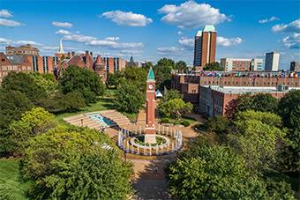 An aerial photo of the iconic brick clock tower on SLU's campus, shot on a sunny day.