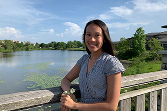 Chaifetz school senior Olivia Tran, wearing a blue and white striped dress, smiles. She is outside on a sunny day and a lake and trees are visible in the background.