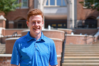 Sophomore Service Leadership student Patrick Holbrook poses for a photo in the sun in front of the flowing fountains along the steps leading to John and Lucy Cook Hall, home to Saint Louis University's Chaifetz School of Business.