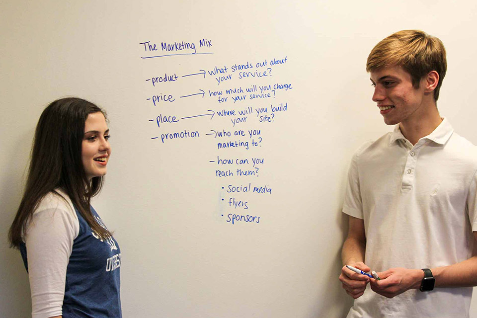 Chaifetz School students write business strategies on a whiteboard while serving as mentors during college access program hosted by St. Louis Internship Program at the Chaifetz School of Business.