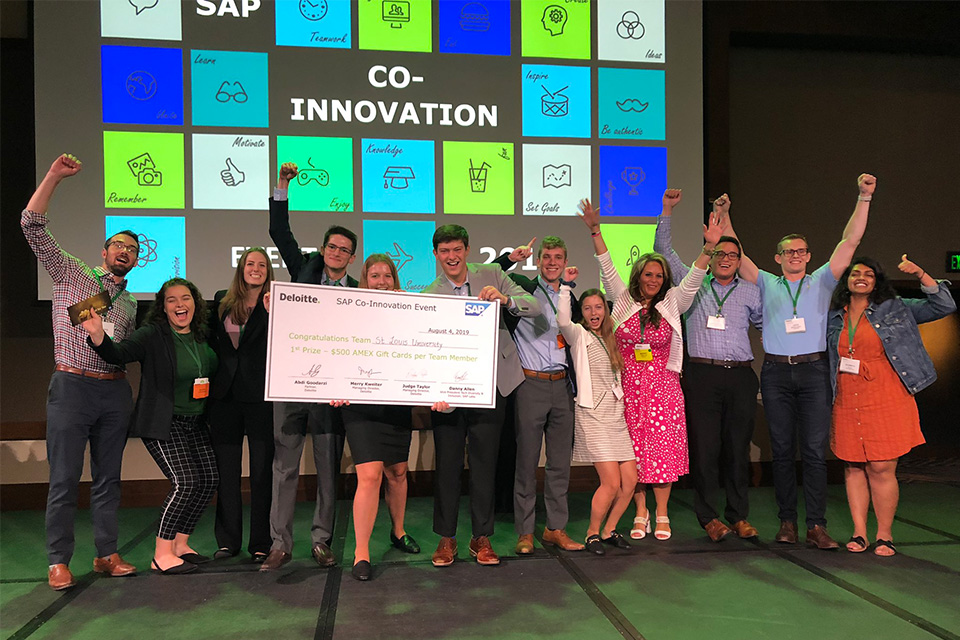 Chaifetz Students celebrate on stage with giant check after winning the 2019 Deloitte-SAP Co-Innovation Event