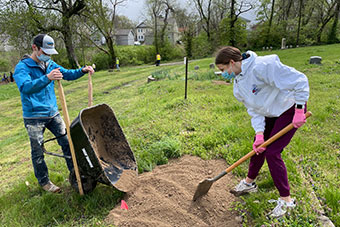 Two SLU students, wearing face masks, shovel mulch outside as part of a Service Day activity.