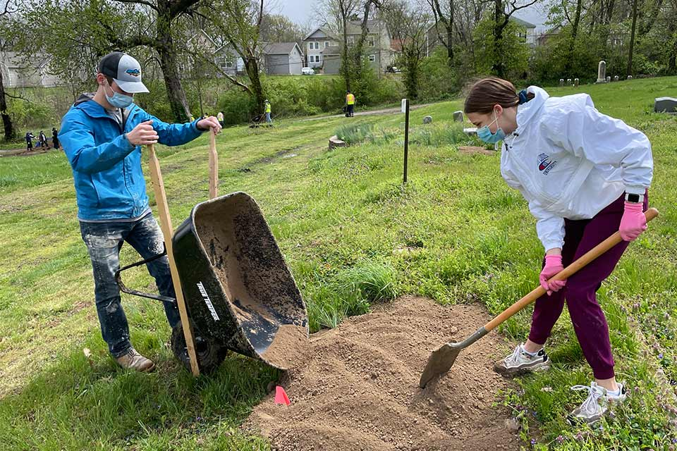 Two SLU students shovel dirt outdoors as part of a Service Day activity.