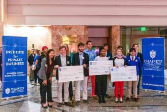High school students who won the 2019 Teen Elevator pose with other finalists as oversized checks are presented to the winners.
