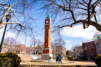 A wide shot of SLU's brick clock tower on a sunny winter day. Students, wearing face masks, walk past the tower on their way to class.