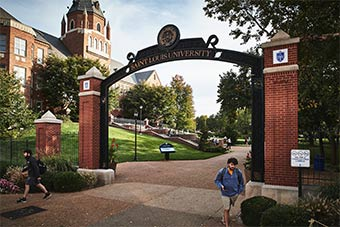 A student walks under a metal arch that says SAINT LOUIS UNIVERSITY with the university's seal. Cook Hall is visible in the background.