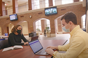 Students in the Chaifetz School's One-Year MBA program study in the Shannahan Atrium of Cook Hall.