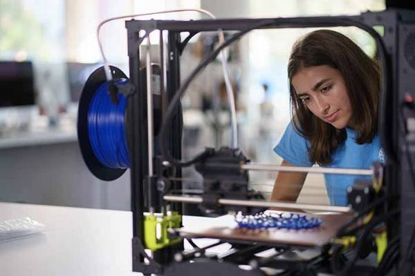 A SLU student using a 3D printer