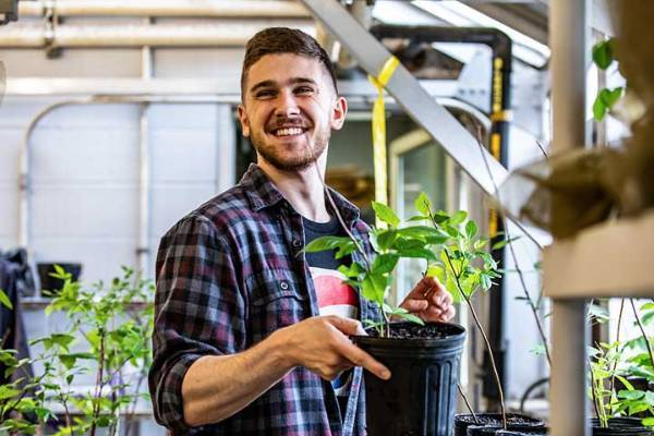 Student with plant in lab