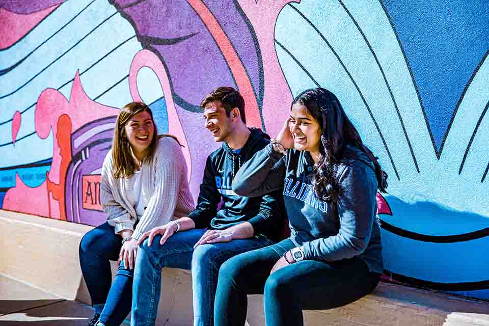 Students sitting in front of a mural