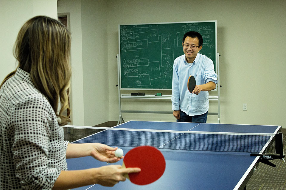 Miao Zhang plays ping-pong with SLU LAW faculty and students during the 2017 Ping Pong Tournament.