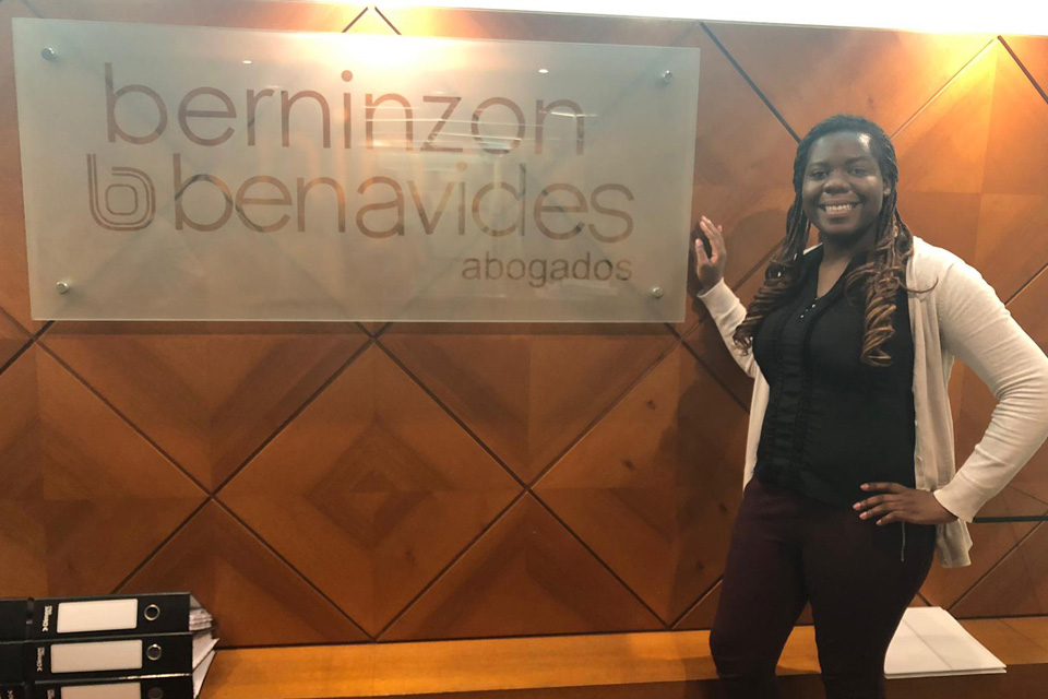 Codi Cox poses in front of the Berninzon & Benavides Abogados sign.