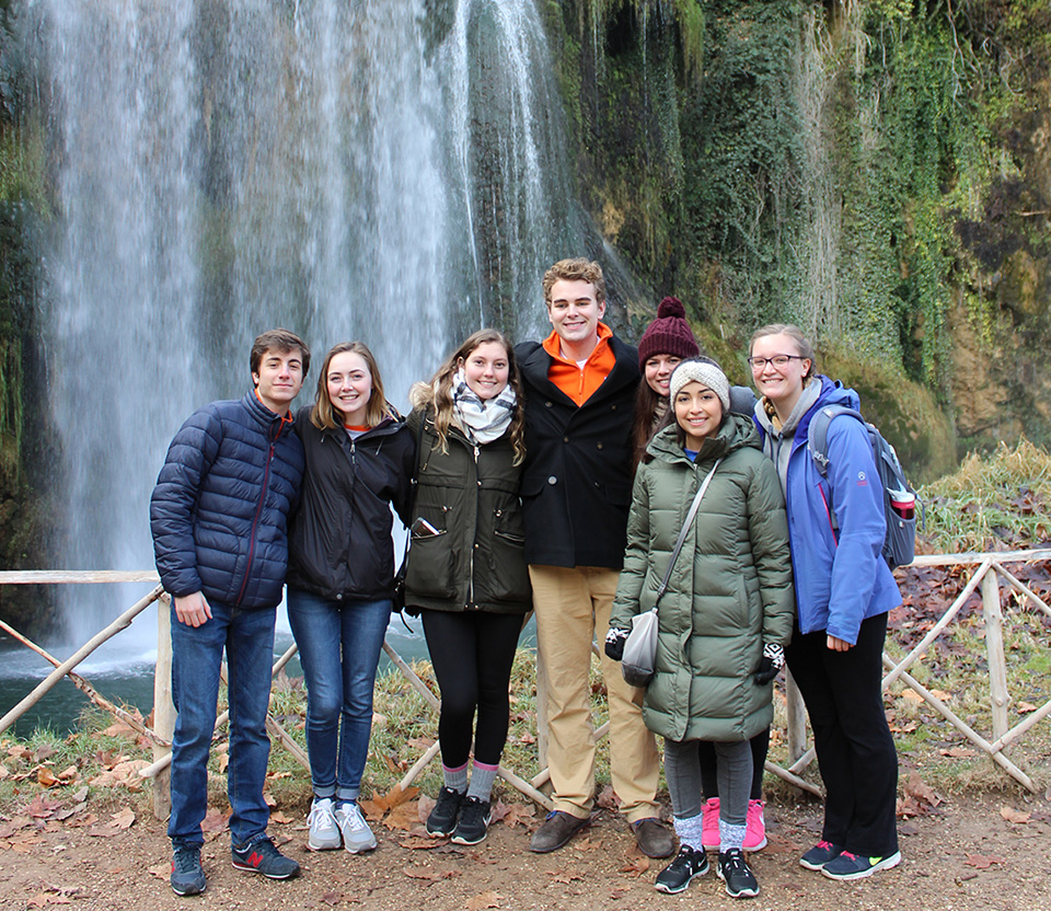 Students pose in front of a waterfall at the scenic Monasterio de Piedra.