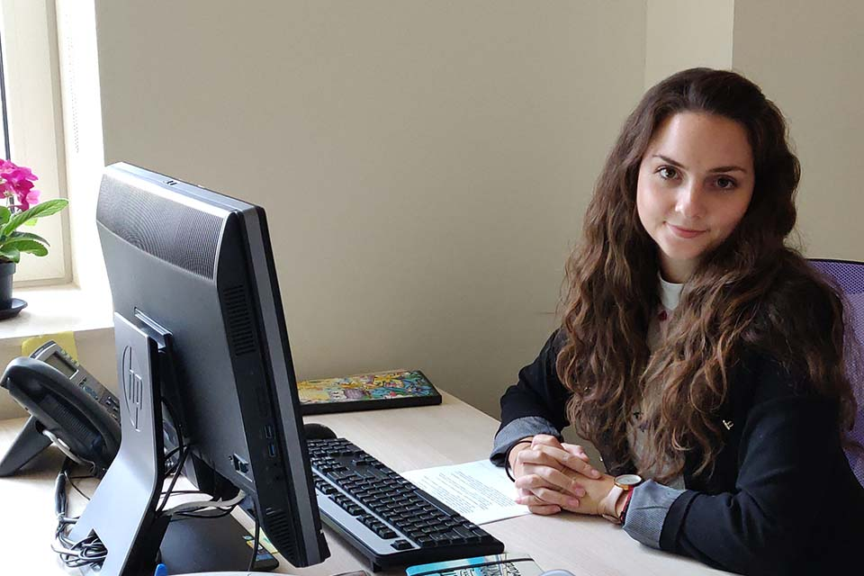 Izabel Trizlova poses for a photo at her desk at the American College of Bulgaria.