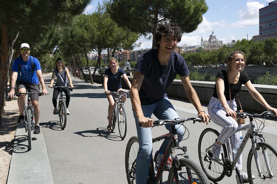 "Cultural programming is enhanced during the summer sessions, to assure that time outside of the classroom is enriching and engaging. (Above) Students take a bicycle tour of the Madrid Río Park, a recreational area along the Manzanares River which boasts panoramic lookout points to take in views of the Royal Palace, both modern and historic bridges and the so-called ""Madrid Río Beach."""