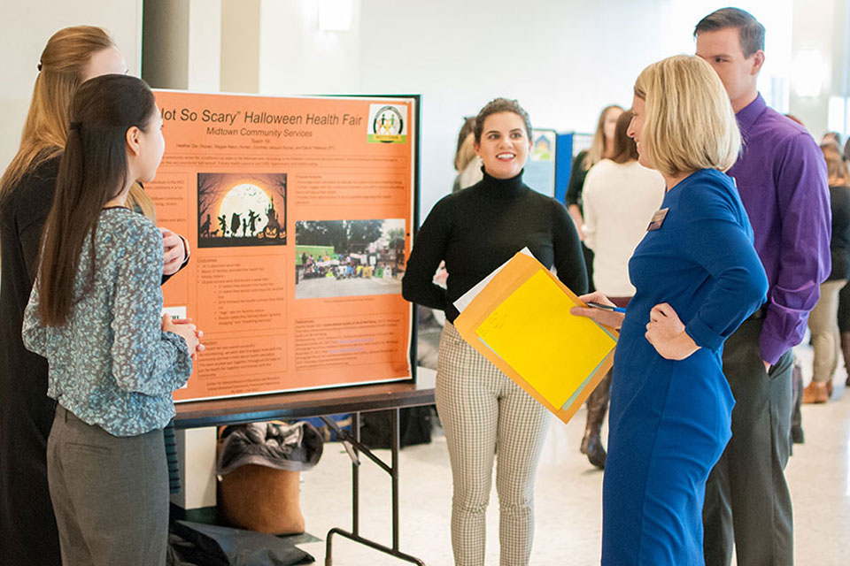 Students presenting posters that showcase their projects to help community organizations improve health outcomes