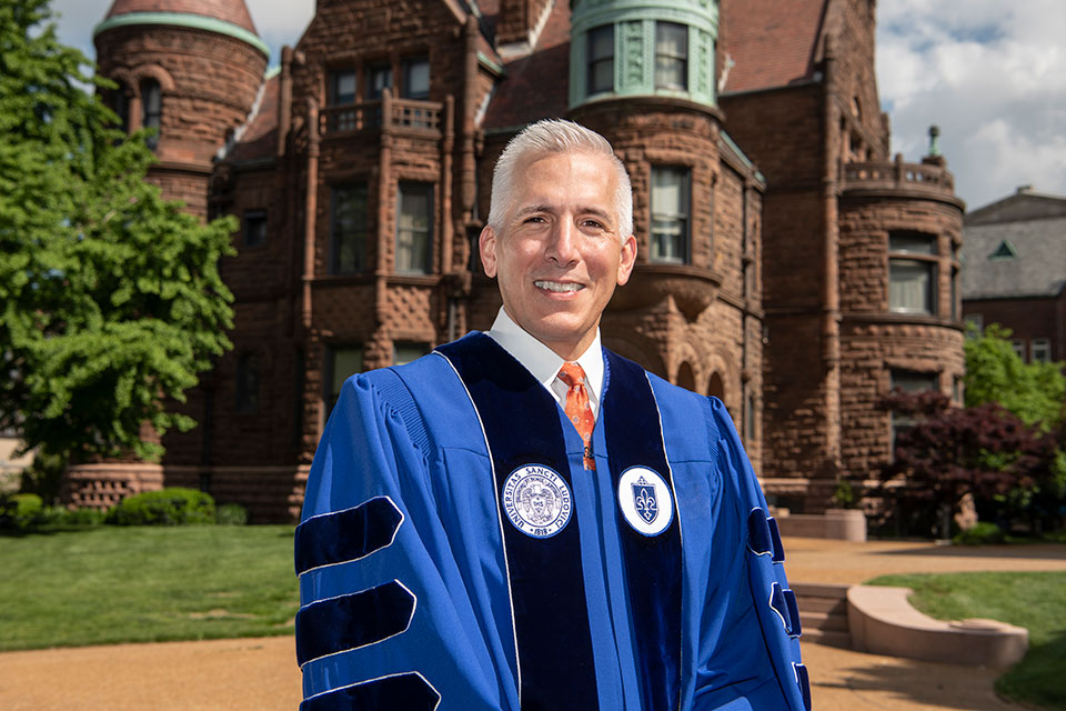 Saint Louis University alumnus and this year's commencement speaker Alexander Garza, M.D., poses for a photo in academic regalia while visiting SLU's campus.