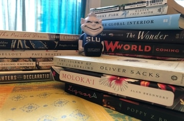 The Billiken sits atop a stack of novels.