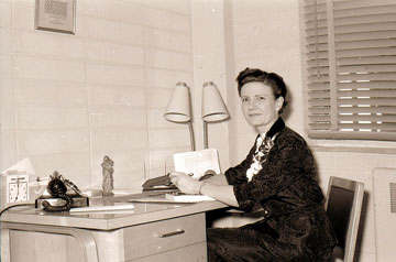 Dame Mary Bruemmer in a 1950s archival photo working at her desk and facing the camera.