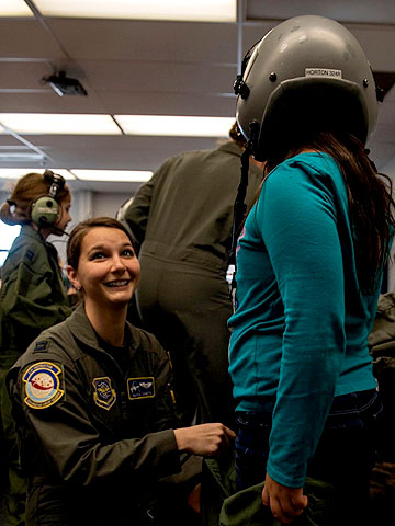 Alicia Canetta helps a student try on a flight helmet