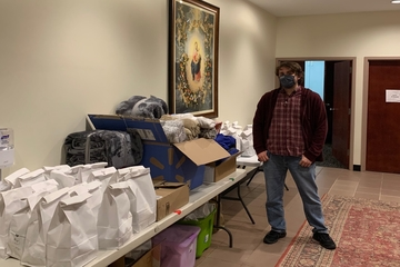 SLU student Andrew Sweeso, president of SLU's St. Benedict Labre Ministry with the Homeless, stands with donations for people experiencing homeless as part of the Catholic Studies Centre's care package night.