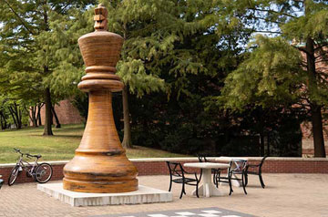 A photo of the Chess Piece statue in front of Morrissey Hall.