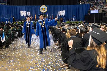 University President Fred P. Pestello, Ph.D., waves to new graduates.