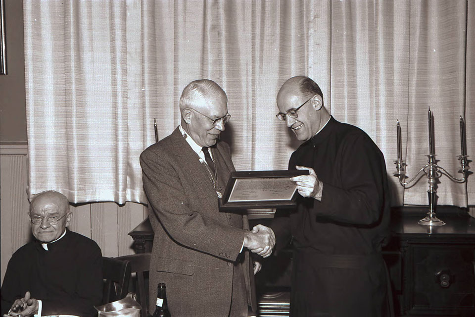SLU research Edward Doisy, Ph.D. (second from left) shows his Nobel Prize to University President Patrick Holloran, S.J. (right) as Alphonse Schwitalla, S.J., looks on (far left).