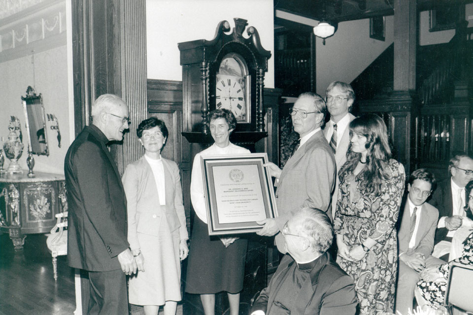 Edward A. Doisy, Ph.D. (holding plaque at right) gathers with his family and SLU leaders to receive an honor.