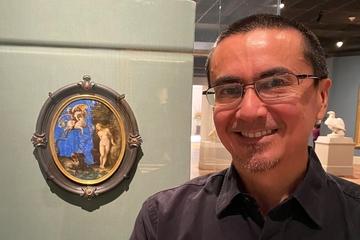 John Encarnacion, Ph.D., a geologist at Saint Louis University, stands before a painting on lapis lazuli of Andromeda and Perseus at the Saint Louis Art Museum.