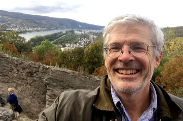 Thomas Finan, Ph.D., a professor of history and archaeologist at Saint Louis University, poses in front of a castle while smiling.