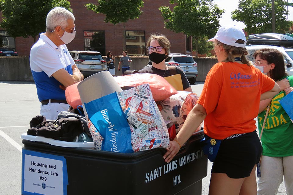 SLU President Fred P. Pestello, Ph.D., left, greets a new student during Move-In Thursday, Aug. 19, 2021. Photo by Joe Barker.