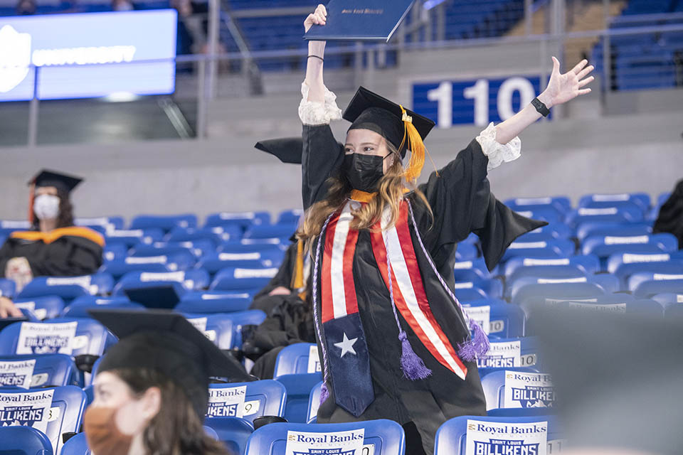 A Saint Louis University graduate celebrates at a precommencement ceremony Wednesday, May 19, at Chaifetz Arena. Photo by Steve Dolan.