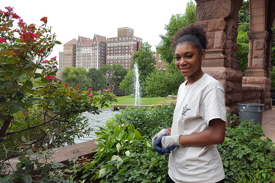 Heaven Persaud, a student worker in the grounds services department, maintains the butterfly garden outside of Cupples House.