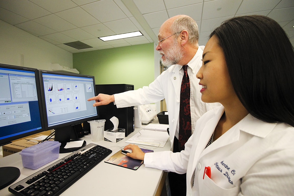 Daniel Hoft, M.D. Ph.D., and Catherine Cai review data that shows detailed information about characteristics of individual T cells at SLU flow cytometry research core.