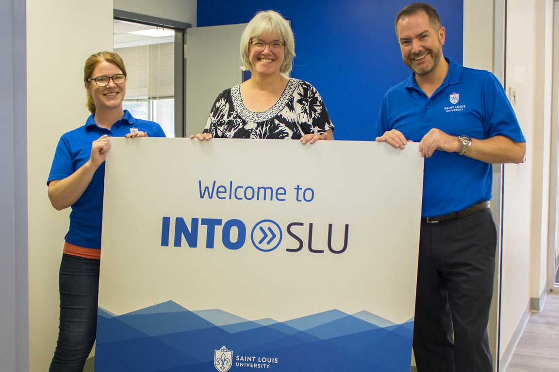 Annie Rosenkranz, director of student experience; Anneke Bart, Ph.D., academic director; and Tim Hercules, J.D., M.I.B., executive director of INTO Saint Louis University, hold the