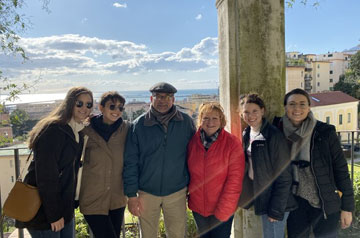 Students and instructors pose at the Garden of Minerva as part of Saint Louis University's Mediterranean Diet Trip in Salerno, Italy. The group stands before ruins and a view of the town.