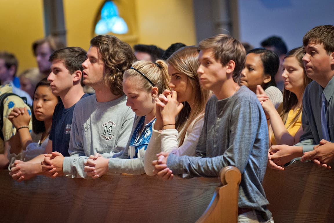 Students kneel to pray during Mass.
