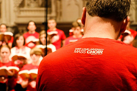 The SLU Mass choir with a back view of a choir member's shirt.