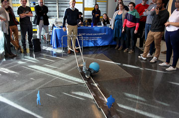 A student rolls a ball down a shoot at a competition during Parks College's celebrations of National Engineers Week.