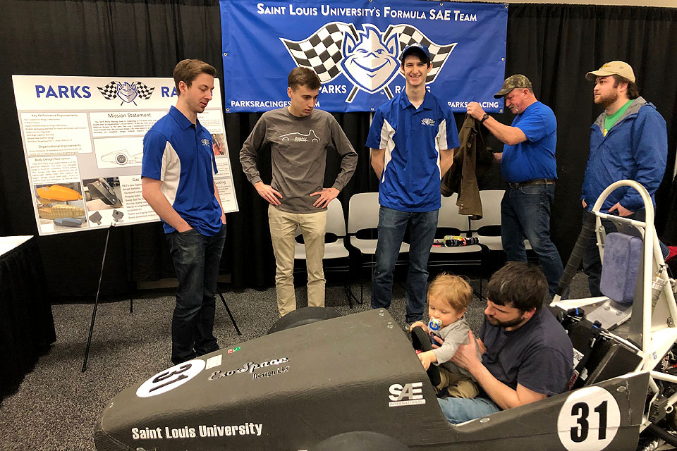 A future Billiken gets a feel for the controls in the Parks Racing Club's car at the St. Louis Auto Show.