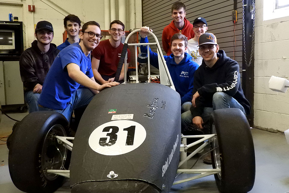 Members of the Parks Racing FSAE club pose with their black and white race car.