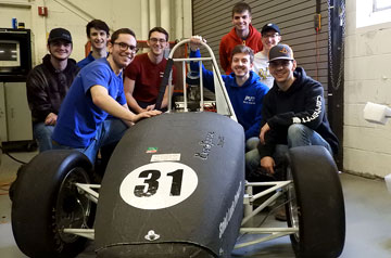 Members of the Parks Racing FSAE Club pose with their newly-built race car in Oliver Hall on the campus of Saint Louis University.