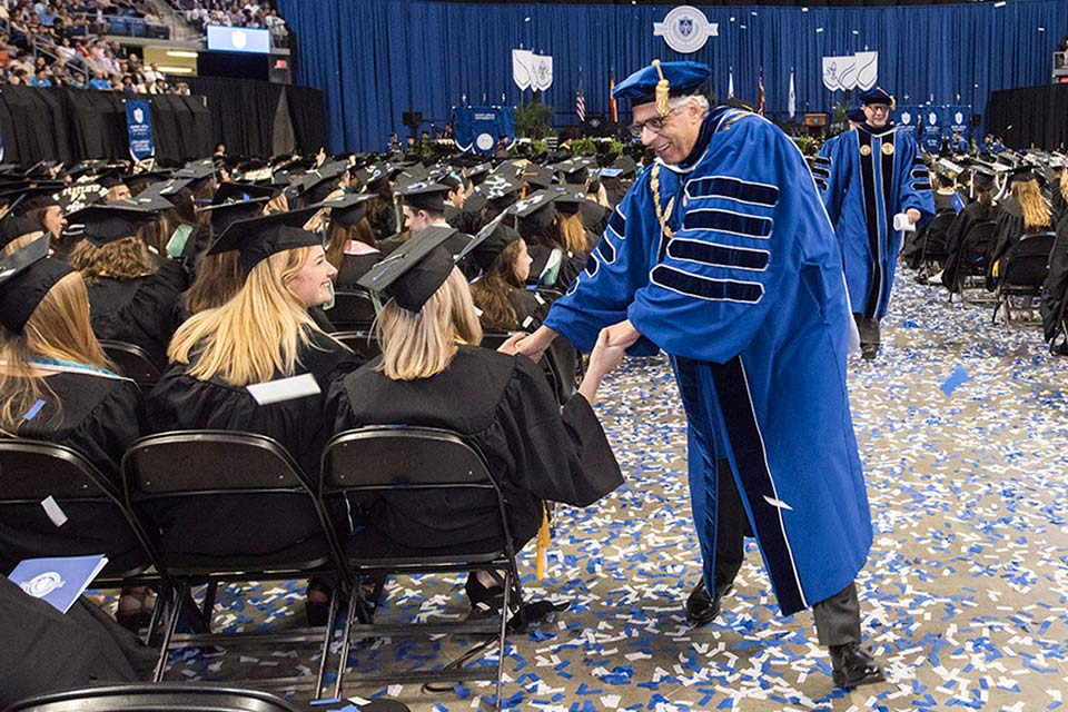 Dr. Pestello greets students at commencement